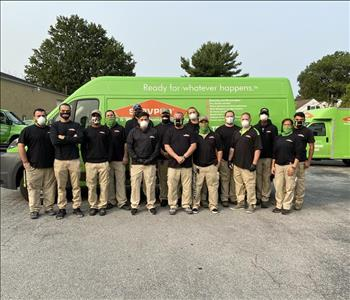 Group of men & women standing in uniforms and masks in front of SERVPRO trucks