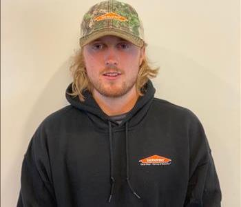 Young man standing with SERVPRO sweatshirt and hat on
