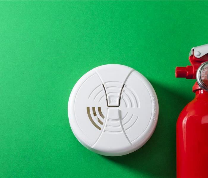 A fire extinguisher, and fire alarm laying on a green backgruond.
